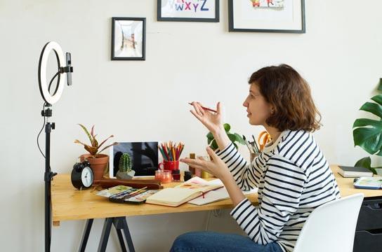 Kevytyrittäjä kuvittaja kuvaamassa videoblogia työstään.