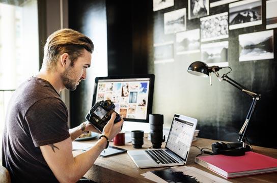 Kevytyrittäjä valokuvaaja siirtämässä kamerasta kuvia tietokoneelleen.